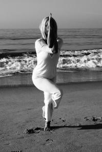 Angela Kukhahn in 'eagle' pose a yoga asana on the beach in santa monica ak