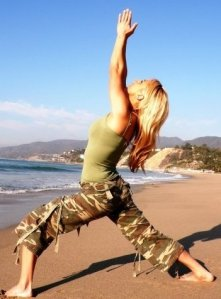 Angela Kukhahn in Warrior 1 pose (Vhirabhadrasana 1) on the beach. Photography by Leelu Morris