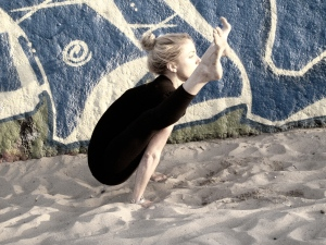 Angela Kukhahn at the beach in yoga arm balance Tittibasana photo by Leelu Morris